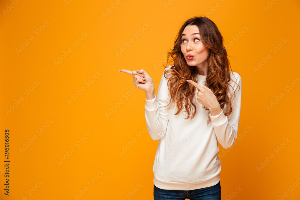 Fototapety, obrazy: Funny brunette woman in sweater looking and pointing away