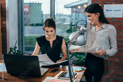 Young personal assistant discussing plans with boss in her office Canvas Print