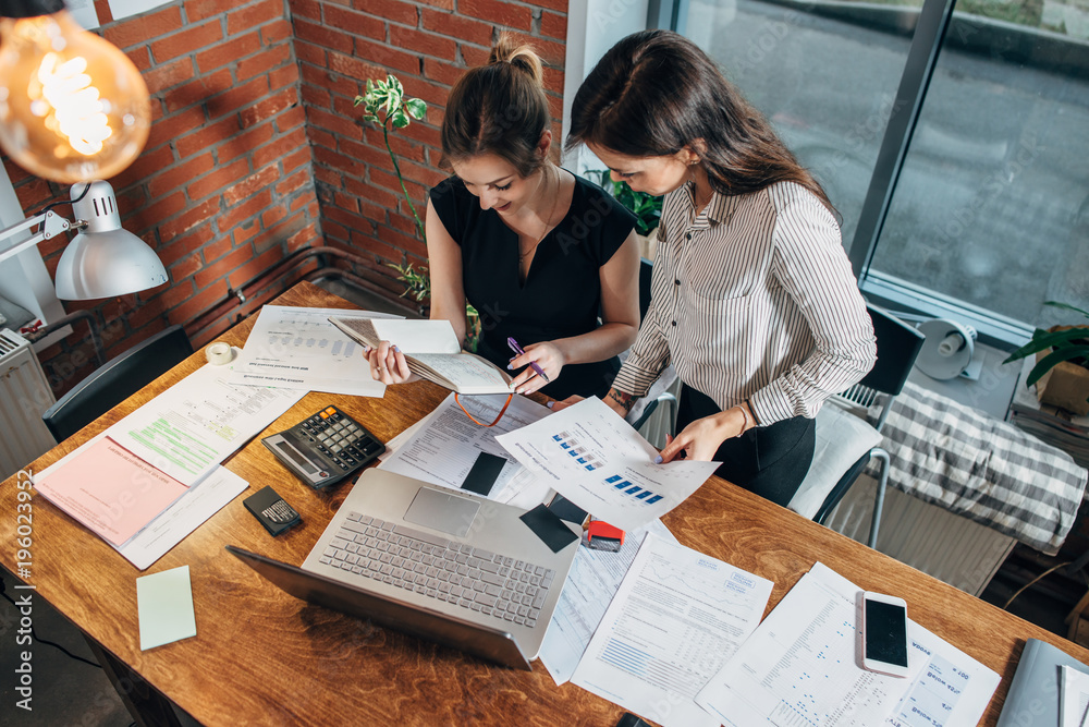 Fototapety, obrazy: Top view of two female colleagues and desk covered with papers and documents. Businesswomen studying the data working on new sales strategy
