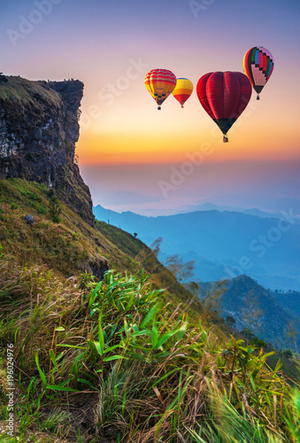 Poster Montgolfière / Dirigeable Colorful hot-air balloons flying over the mountain at Phucheefa, Chiangrai province , Thailand.