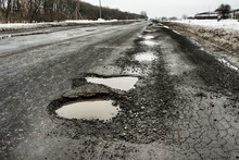 Road Is Paved With Cracks In Pits And Puddles From Snow. Landscape Of Winter Road In Cloudy Gray Weather. Concept Of Road Repair