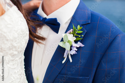 f1ddc3250556 Bride and groom with wedding boutonniere from blue hydrangea, white rose,  lilac flowers outdoor