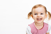 A Very Happy And Excited Toddler Girl With Ponytails Laughing And Showing Teeth, Isolated On White Studio Background