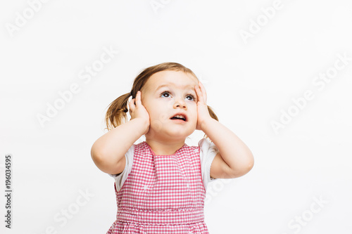 Fotografie, Obraz  Preschool toddler girl  holding her head and looking up,  isolated on white back