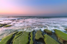 Sunset At The Beach With Natural Coastal Rocks And Waves Trails. Nature Composition.
