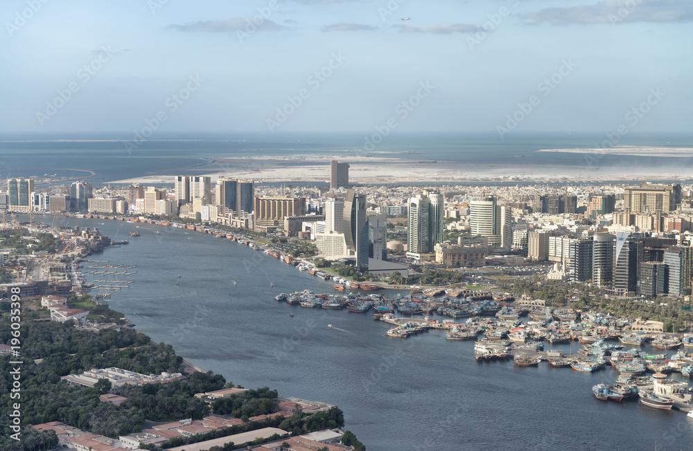 Fototapeta Aerial city skyline and creek from helicopter, Dubai