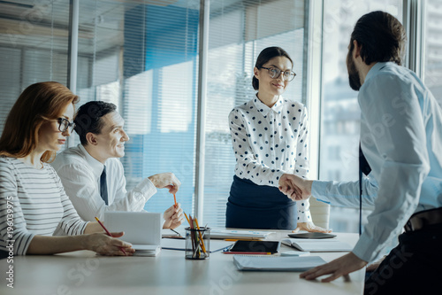 Fototapety, obrazy: Business etiquette. Charming young businesswoman shaking hands with her male colleague while having a meeting with the other partners