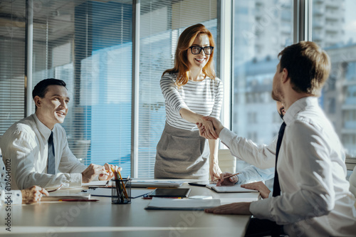 Obraz Best cooperation. Charming young woman carrying out a meeting with her companys business partners and shaking hands with a new one - fototapety do salonu