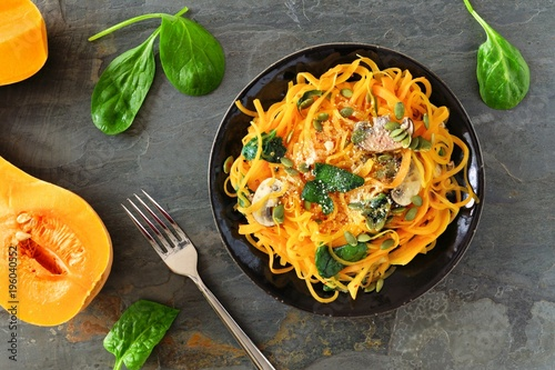 Cuadros en Lienzo Butternut squash spirilized noodles with spinach and pumpkin seeds on dark slate background, Healthy eating concept