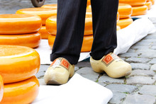 Young Woman And Older Man Legs In Wooden Dutch Klomp Shoes On A Old Town Cheese Market In Gouda, Holland