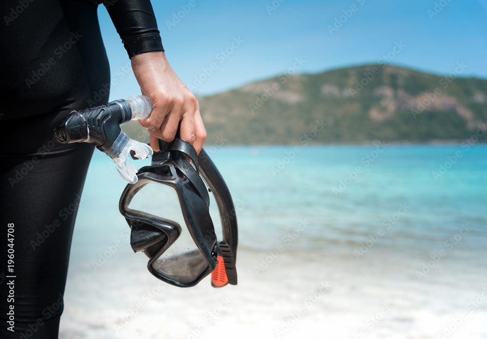 Fototapeta Diving goggles and snorkel gear in hand near beach