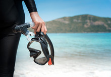 Diving Goggles And Snorkel Gear In Hand Near Beach