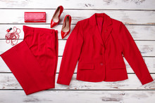 Flat Lay Red Women Suit And Accessories. Jacket, Trousers, Wallet, Shoes, Necklace Beads And Lacquer. Bright Wooden Desks Surface Background.