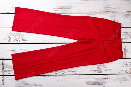 Obraz na plátne Fashion red pants on white wooden background