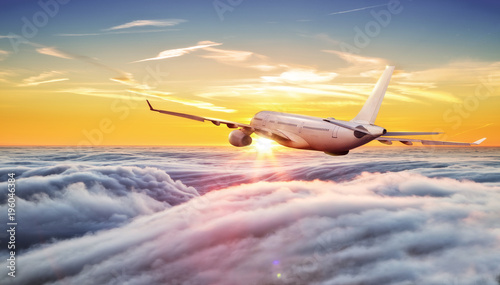 Poster Avion à Moteur Big commercial airplane flying above clouds in sunset