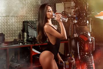 Fototapeta na wymiar Girl drinking water in garage