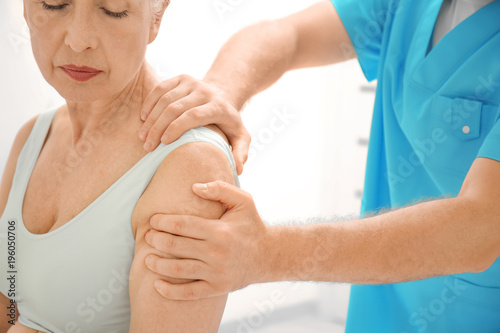 Fotografía Elderly woman getting shoulder massage at physical therapy office