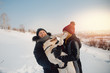 Man and young woman play with labrador in winter, wearing winter hat and jacket. Concept of love and friendship, walk