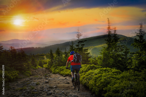 Mountain biker riding at sunset on bike in summer mountains forest landscape. Man cycling MTB flow trail track. Outdoor sport activity.