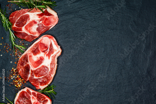 Fotografie, Obraz  Raw juicy meat steaks ready for roasting and vegatables on a black board background