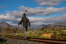 A Land Surveyor Walking With A Trimble Gps Rover Survey Equipment Wih Dark Clouds Behind Him