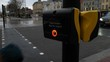 Pedestrian pushes the traffic signal button on an urban rainy day. Close up.