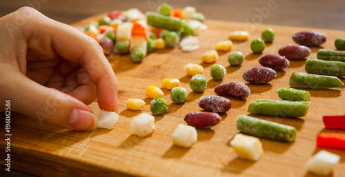 woman's hand collects even row of colorful Frozen mixed vegetables on a wooden background Wallpaper Mural