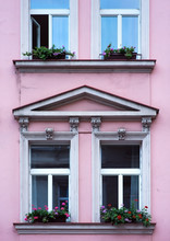 Facade Of A Residential Building In Vintage Style. The Windows Are Decorated With Flowers