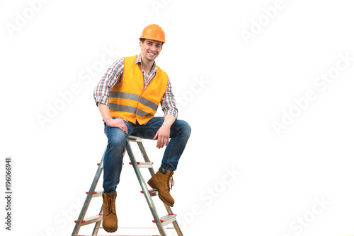 The happy builder sitting on the ladder on the white background