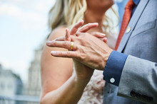 Mid Section Of A Newlywed Couple Holding Hands