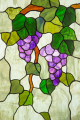 Fototapeta Witraże świeckie A stained glass panel depicts ripe purple grapes on a vine with green leaves.