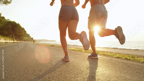 SUN FLARE: Unknown jogging couple enjoys the warm summer afternoon sun rays.