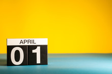 April 1st. Day 1 Of April Month, Calendar On Table With Yellow Background. Spring Time, Empty Space For Text