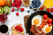 English breakfast - fried egg, beans, tomatoes, coffee, bacon and toast with orange juice, fresh fruits and berries