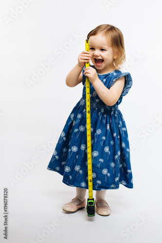 Fotografering  Cute child smiling and holding a measuring tape, they grow fast