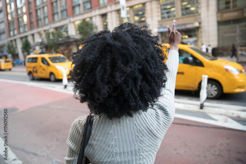 Tablou Canvas Woman hailing a taxi cab on a busy city street