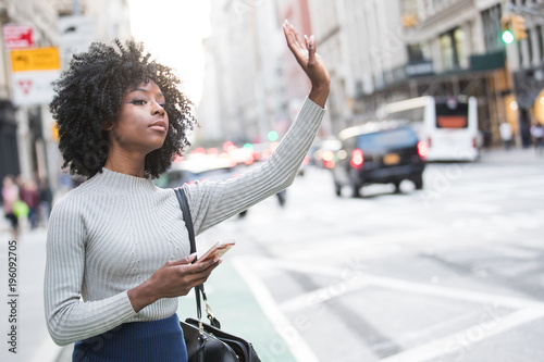 Fotografija Woman hailing taxi cab or ride share car service in New York