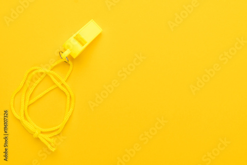 Fotografering  plastic referee whistle on the yellow background with copy space