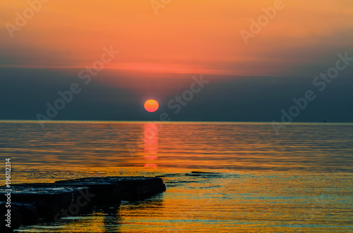 Foto op Plexiglas Oranje eclat orange red sun rises above the golden waves of the ocean