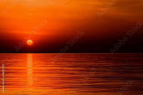Foto op Plexiglas Oranje eclat Crimson red sunrise of the orange sun over the ocean