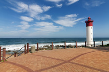 Walkway With Metal Barrier Against Red And White Lighthouse