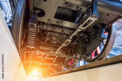 View of the locomotive from underneath the wheels on the between the rails, view from the repair pit.