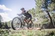 Male cyclist splashing water with mountain bike