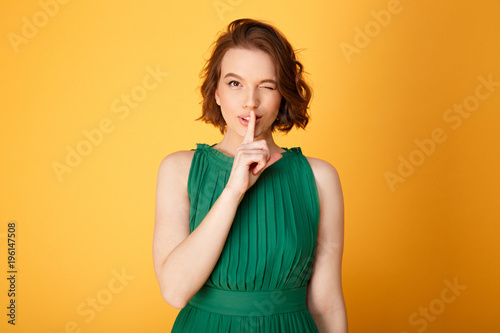 Photo  portrait of attractive woman showing silence sign isolated on orange