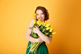 Fototapeta Tulipany - portrait of smiling woman with bouquet of yellow tulips in hands isolated on orange