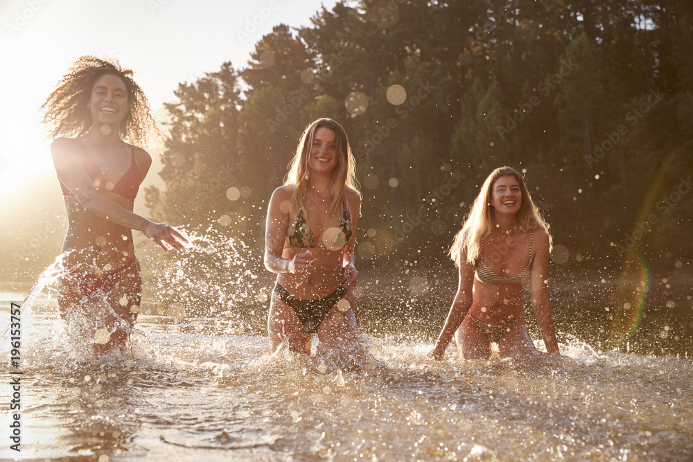 Fototapety, obrazy: Three female friends on vacation having fun in a lake