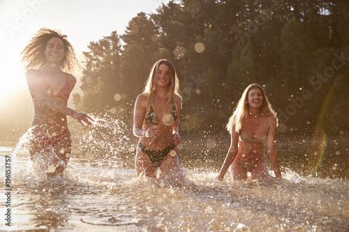 Fotografie, Obraz  Three female friends on vacation having fun in a lake
