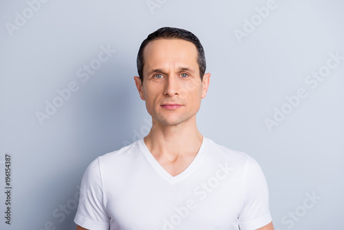 Fotomural Portrait of trendy, neat, shaven, brunet man in white t-shirt with serious expre