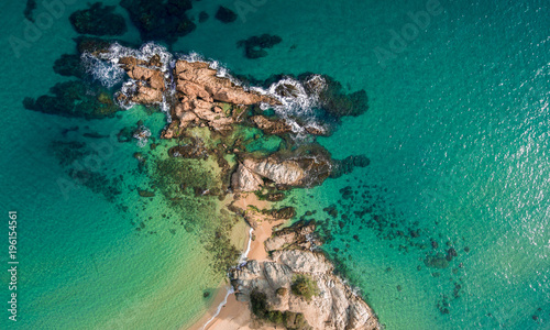 Aerial views of the rocks in the sea on a sunny day.