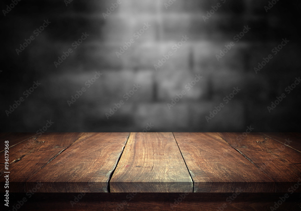Fototapety, obrazy: Old wood table with blurred concrete block wall in dark room background.
